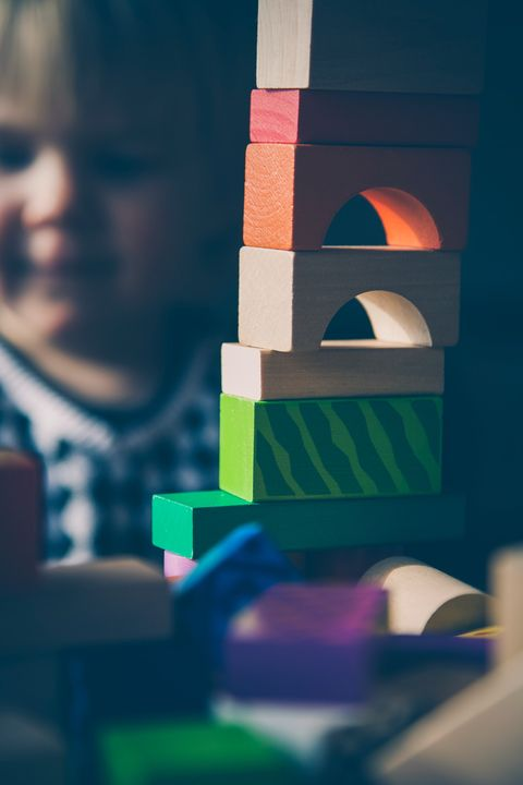 Child building a tower with wooden blocks