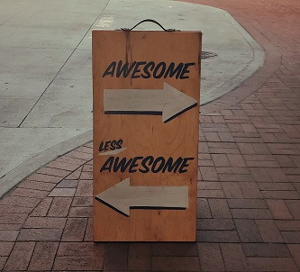 "Sign on a pavement with the word ""awesome"" above an arrow pointing to the right, and the words ""less awesome"" above an arrow pointing to the left"