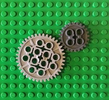 Image of a large and small lego cog on a green lego base